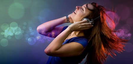 dance music: Young girl having fun at a disco or nightclub with retro headphones listening to music