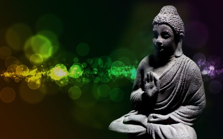 Generic zen stone buddha statue with light shinning on the figure Stock Photo