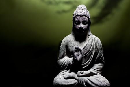 stone buddha: Generic zen stone buddha statue with light shinning on the figure Stock Photo