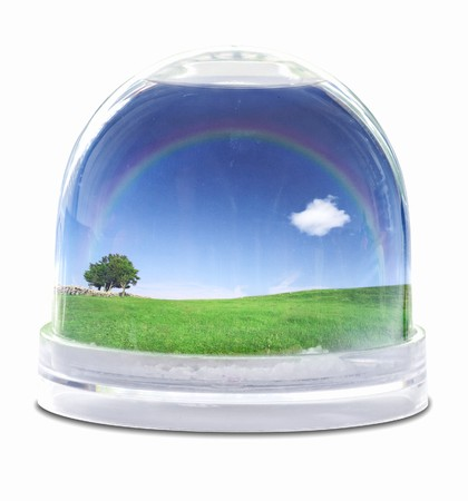 Snow globe with green grass field, blue sky fully white cloud and lone tree photo