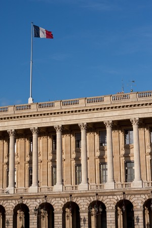 elysees: French flag flying in Paris, France on a national historic building along Champs Elysees Stock Photo