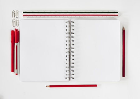Open notebook with various stationeries or office supplies, white blank pages photo