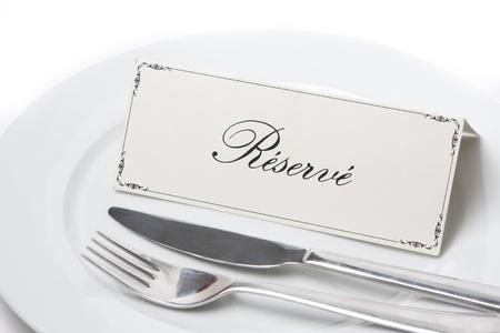 reservacion: Inicio de sesi�n reservada gen�rico en un plato blanco con cuchillo y tenedor Foto de archivo