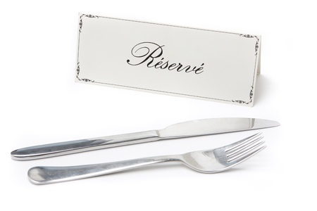Generic reserved sign in french with fork and knife on white background photo
