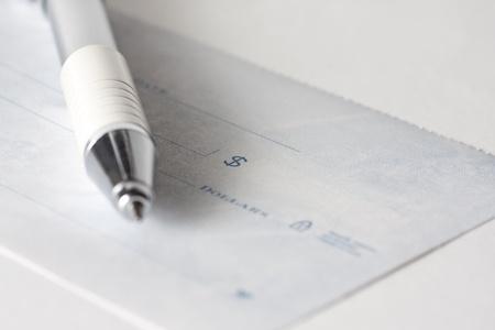 Un cheque o cheque de cerca con un lápiz Foto de archivo - 9763522