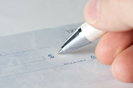 Close up shot of a cheque or cheque with a pen photo