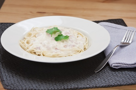 Spaghetti carbonara with bacon, cream and cheese sauce served on a white plate photo