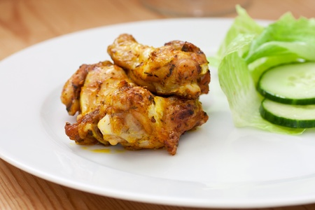 Crispy delicious spicy roasted chicken on a white plate photo