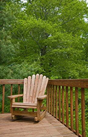 adirondack: Adirondack chair on deck against forest background