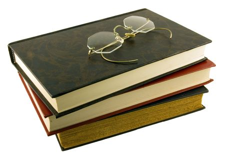 Vintage glasses atop stack of books Imagens