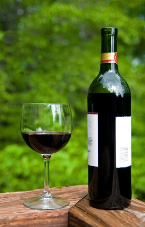 Wine bottle and glass on wood deck against forest background