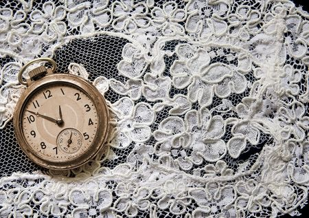 Antique pocket watch on white lace