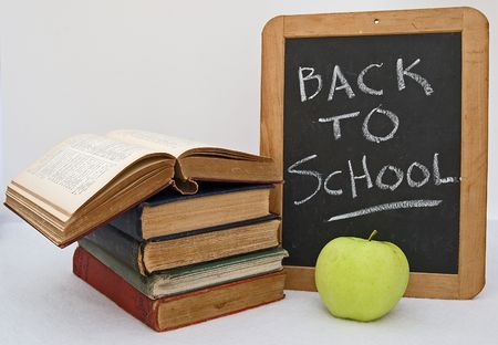 Back to School sign with stack of books and green apple Imagens