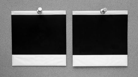 Two instant prints pinned to gray wall