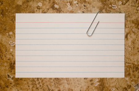 Single lined note card and paper clip on brown stone background