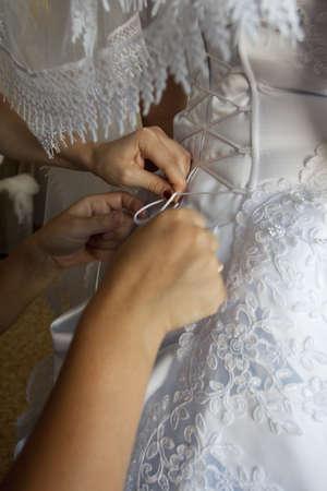 To the bride fasten a wedding dress Stock Photo - 8954077