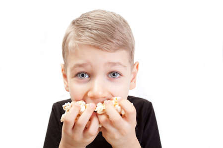 The boy eats popcorn on a white background Stock Photo