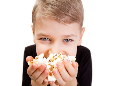 The boy eats popcorn on a white background Stock Photo