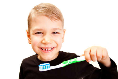 The boy brushes teeth a brush on a white background Stock Photo