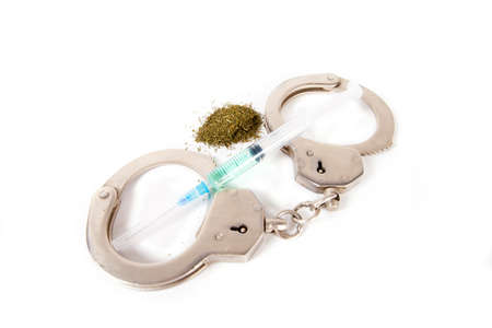 The clasped handcuffs on a white background and a syringe