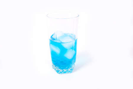 Transparent glass with a blue drink and ice