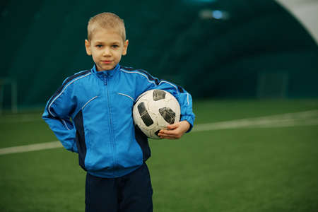 The boy holds a football having a rest from training