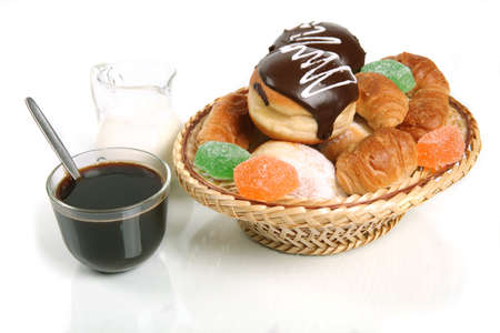 Coffee with milk and a basket with doughnuts and sweets