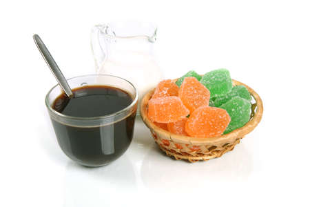 Coffee with milk and fruit candy in a basket