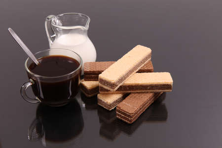 Coffee with milk and wafers against a dark background with reflexion