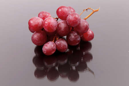 Cluster of red large grapes against a dark background with reflexion