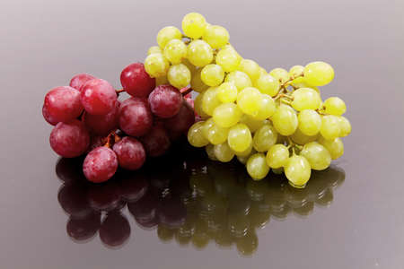 Cluster of red large and green grapes against a dark background with reflexion Stock Photo