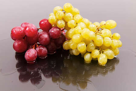 Cluster of red large and green grapes against a dark background with reflexion on water Stock Photo