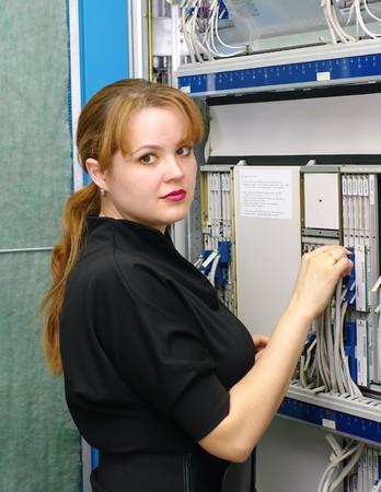 catenation: woman engineer serves equipment on digital telephony station