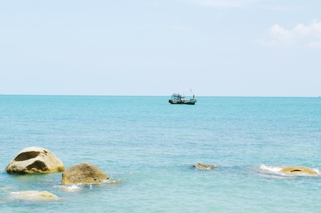 Tropical marine landscape with stones and ship on horizon. Koh Samui Thailand.