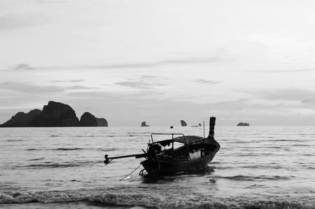 ao: View Andaman sea with longtail boat  in foreground and silhouette of islands on horizon,      Ao Nang beach, Thailand, black-white image. Stock Photo