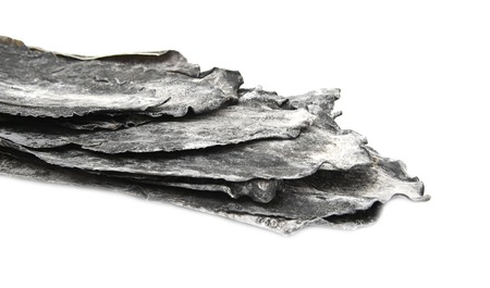 major ocean: Dried leaves of brown seaweed Dashi Kombu on white isolated Stock Photo