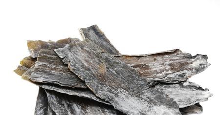 dashi: Dried leaves of brown seaweed Dashi Kombu on white isolated Stock Photo