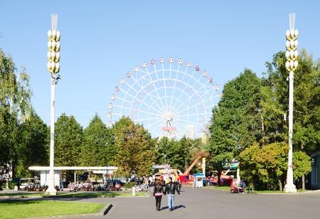 enea: MOSCOW, RUSSIA - SEPTEMBER 16, 2014: ENEA VDNH,VVC,leisure area,amusement park, walking people, view of Ferris wheel