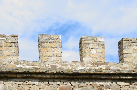genoese: Merlons of ancient stone wall closeup, against blue cloudy sky, Sudak Genoese fortress Crimea