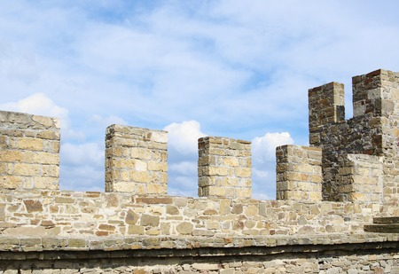 sudak: Merlons of ancient stone wall closeup, against blue cloudy sky, Sudak Genoese fortress Crimea