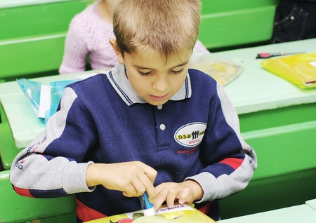 Omsk, Russia - September 24, 2011: schoolboy makes applique at school desk on lesson in classroom