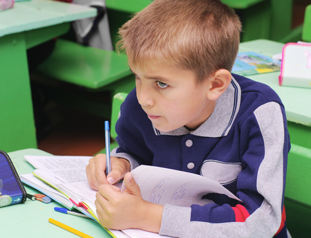 Omsk, Russia - September 24, 2011: schoolboy at school desk on lesson in classroom closeup