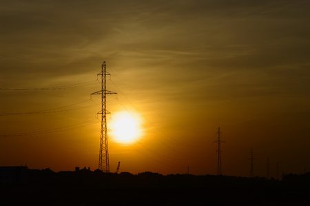three phase: Outlines of masts of high voltage power lines in sunset light