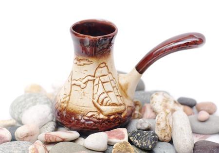 cezve: ceramic coffee cezve on multi-coloured pebbles Stock Photo