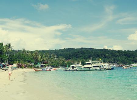 passenger ships: KRABI, THAILAND - OCTOBER 27, 2013:  Ton Sai Bay of  Andaman sea, Phi Phi Don island beach with people,      passenger ships  at shore, toned image