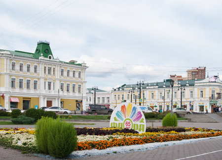 former years: Omsk, Russia - September 20, 2016: Jubilee flowerbed  Flora of 65 years,  organ hall and former merchanttrading house