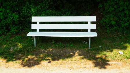 restfulness: white painted park bench in the shadow