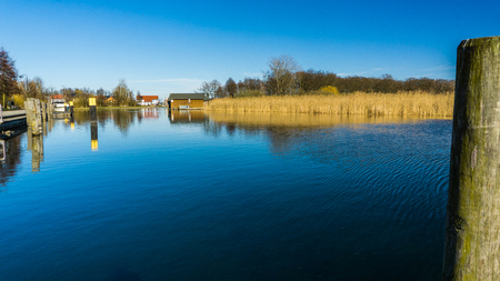 still river with boathouses Stock Photo