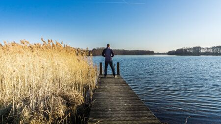 man standing on jetty at a lake