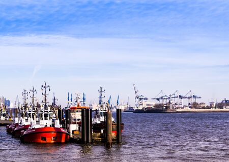 Hamburg, germany - February 2019 Hamburg harbor with several tugboats tied to a pier and cranes in background